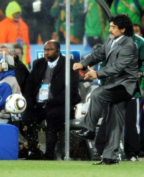 Diego Maradona can't resist a kick from the touchline