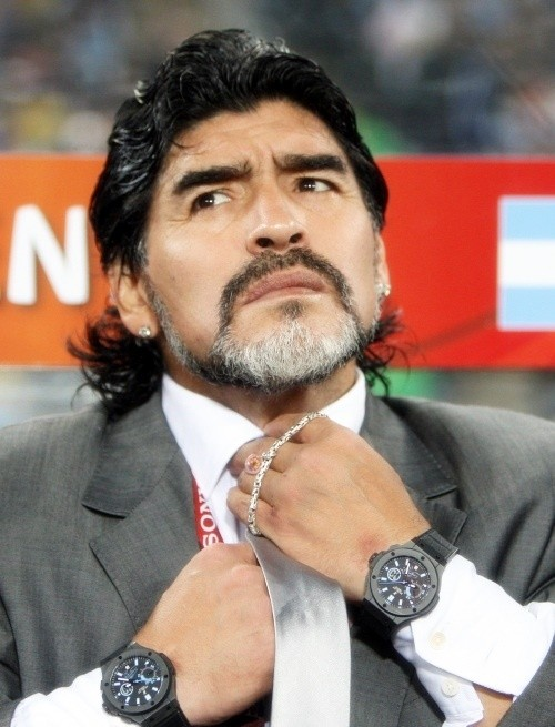 Diego Maradona adjusting his necktie wearing a suit picked by his daughters