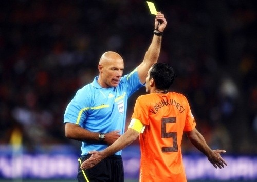 Howard Webb had a busy night with 12 yellow cards and one red. Here he is with Giovanni Van Bronckhorst