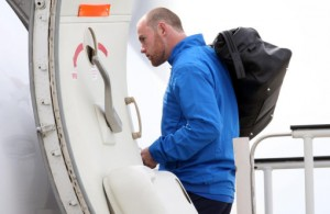 Rooney boards the plane for Switzerland