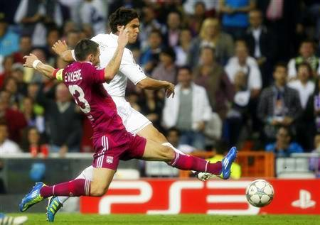 Real Madrid's Kaka shoots past Olympique Lyon's Reveillere during their Champions League soccer match at Real Madrid's Santiago Bernabeu stadium