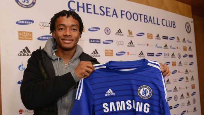 Juan Cuadrado holding a Chelsea shirt after completing his transfer