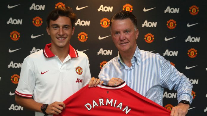 Darmian holding the Manchester United shirt with Van Gaal after completing transfer