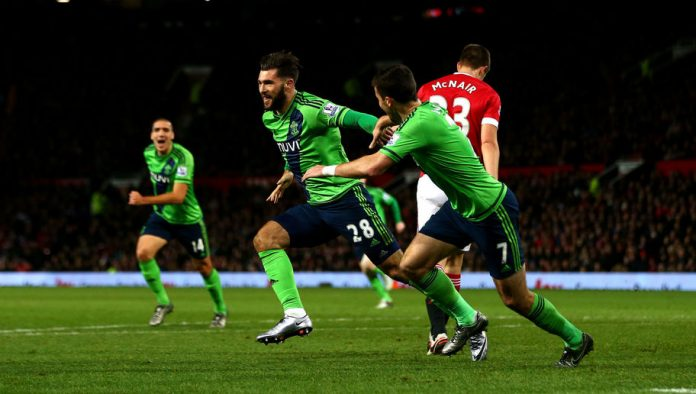 MANCHESTER, ENGLAND - JANUARY 23: Charlie Austin (C) of Southampton celebrates scoring his team's first goal with his team mate Shane Long (R) during the Barclays Premier League match between Manchester United and Southampton at Old Trafford on January 23, 2016 in Manchester, England. (Photo by Michael Steele/Getty Images)