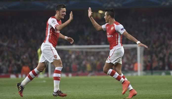 Arsenal's Alexis Sanchez, right, celebrates after scoring against Galatasaray with his teammate Mesut Ozil during the Champions League Group D soccer match between Arsenal and Galatasaray , at the Emirates Stadium in London, on Wednesday, Oct 1, 2014. (AP Photo/ Tim Ireland)
